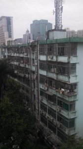 Apartment building with laundry and air conditioners and detritus.